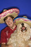 Dog and man wearing sombreros. Fluffy brown dog and Caucasian male young adult wearing Mexican sombreros stock images