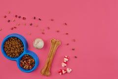 Dog mellanmål, hundtuggningar, hundbenet, bollleksaken för hund på en rosa bakgrund med kopieringsutrymme Arkivfoton
