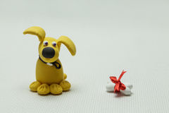 Dog a mongrel and a bone from plasticine Royalty Free Stock Image