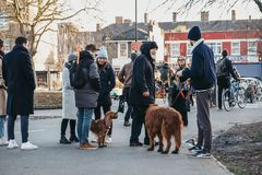 Dog owners chatting in Haggerston Park in Hackney, East London, UK. London, UK - February 3, 2019: Dog owners chatting in Haggerston Park in Hackney, East London stock images