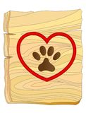 Dog paw print in heart on wooden Board. Royalty Free Stock Photography