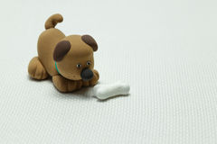 Dog from plasticine and a bone Royalty Free Stock Photo