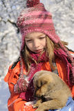 Dog playing with girl outside. White girl having fun with dog and flakes in snow Royalty Free Stock Image