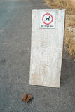 Dog poo. Dog excrement near a no fouling sign Royalty Free Stock Photo