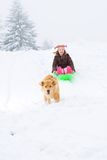 Dog pulling child on a sled Royalty Free Stock Photo