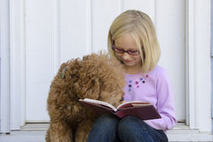 Dog reading with young girl. A young girl reading on the front steps of her house is amused when her dog takes a closer look Stock Photos