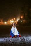 Dog Rhodesian Ridgeback and a Russian flag. On the background of a winter of Saint Basil's Cathedral at night, Red Square, Moscow, Russia Stock Photo
