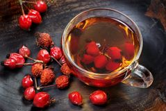 Dog rose berries.dog rose tea. a cup of curative rosehip tea on a wooden table. vitamin tea. remedy for cold and flu. Dog rose berries.dog rose tea. a cup of royalty free stock photography