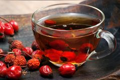 Dog rose berries.dog rose tea. a cup of curative rosehip tea on a wooden table. vitamin tea. remedy for cold and flu. Dog rose berries.dog rose tea. a cup of stock photography