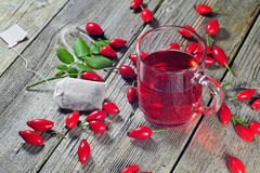 Dog rose tea. Photo of dog rose tea on a wooden table royalty free stock photography