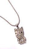 A dog shaped silver colored necklace. Stock Photography