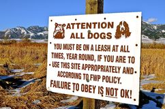 Dog Sign Warning. A sign in front of a mountain range warns dogs to remain leashed Royalty Free Stock Images