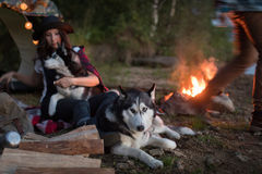 Dog sits by the fire with the hosts and Husky Royalty Free Stock Images