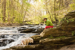 Dog Sitting with man in River Stock Photo