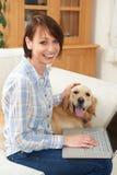 Dog Sitting Next To Female Owner Using Laptop. Dog Sits Next To Female Owner Using Laptop Stock Photography