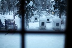 Dog sledding scene: Huts and sleds in Sweden. Swedish winter north of the arctic circle: view from the warm inside out through the window into the cold outside Royalty Free Stock Photo