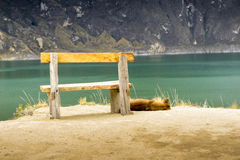 Dog sleeping near wooden chair in front of Quilotoa lake Stock Photography