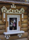 Dog in small wooden house. Dog in small wooden house, peeking out of the window stock image