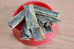 Dog snack crispy salmon skin on bowl Stock Photos