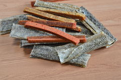 Dog snack crispy salmon skin and chicken soft jerky on table. Dog snack crispy salmon skin and chicken soft jerky on the table Royalty Free Stock Photography