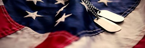 Dog tag chains on flag. Dog tag chains on striped American flag Royalty Free Stock Photo