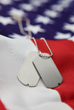 Dog tags. Vertical blank dog tags on American flag with focus on tags - Shallow dof Stock Photo