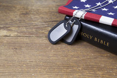 Dog tags with Bible and American Flag. A set of blank silver dog tags on a Bible and American Flag Royalty Free Stock Images