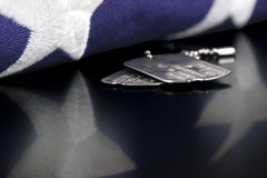 Dog Tags. Or ID tags, once worn by a military verteran with a folded US flag Royalty Free Stock Photo