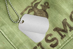 Dog tags on military uniform. Blank dog tags on an old military uniform from the 1960's. Room for copy on the dog tags Royalty Free Stock Photo