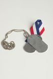 Dog tags and red white blue ri. Military dog tags with a red white and blue ribbon next to them Royalty Free Stock Image