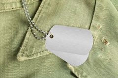 Dog tags on uniform. Blank dog tags on an old military uniform from the 1960's. Room for copy on the dog tags Stock Photos