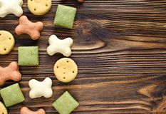 Dog tasty colored biscuits on wooden background with copy space.  Stock Image