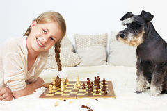 The dog teaches the child to play chess. Royalty Free Stock Photo