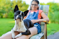 Dog and teenage girl resting in the garden. Sweet Boston terrier puppy on his lady`s lap stock photos