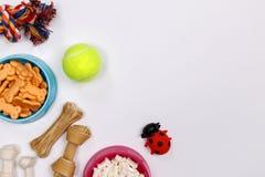Dog tillbehör, mat och leksaken på vit bakgrund Lekmanna- lägenhet Top beskådar arkivfoto