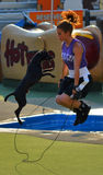 Dog a trainer jumping rope. Dog and a trainer jumping rope on a stage royalty free stock image