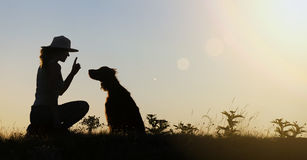 Dog training silhouette. Silhouette of a female as training her dog - website banner Stock Image