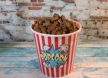 Dog trinkets in a container of popcorn stock image