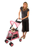 Dog Walk OC Style. Happy young woman who is a loving pet owner taking her pampered pet for a walk Orange County style, in a pet stroller Royalty Free Stock Images
