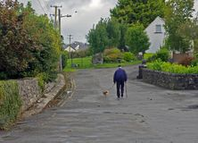 Dog Walker. Old man walking his dog down the middle of a road in Irish Village in Ireland Stock Photos