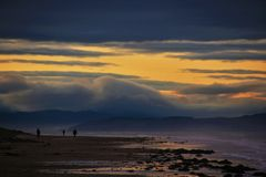 Dog walkers and Sunset at the beach in the North East coast of Scotland. 4 Royalty Free Stock Photo