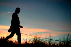 DOG WALKING. Capturing a moment in silhouette of a local walking his dog along the dunes royalty free stock photo