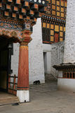 A dog is walking through the courtyard of the dzong of Paro (Bhutan) Stock Photos