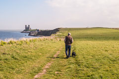 Dog walking, Reculver, Kent, UK. A man walks his dog along a track on the grass on the cliffs heading towards Reculver Towers near to Herne Bay, Kent, UK Royalty Free Stock Photos