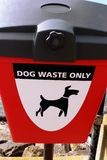 Dog Waste Bin. Dog Waste Only sign on the front of a red bin Stock Photography