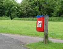 Dog Waste Bin by Park Footpath. Red dog waste buin alongside footpath in park royalty free stock image