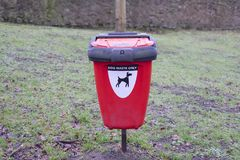 Dog Waste Red Bin in Public Woodland Countryside Park. Dog poo waste only sign on red bin in public park  encouraging owners pick up afterwards Stock Photos