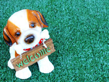 Dog with welcome sign on green background Royalty Free Stock Photography