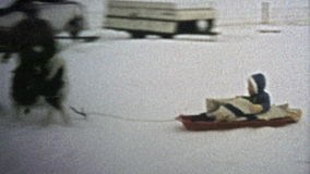 1973: Dog wildly pulling child on winter snow sled.