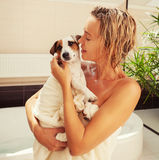 Dog beside the woman in the bathroom Royalty Free Stock Photo